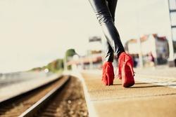 Woman in red high heels walking in train station
