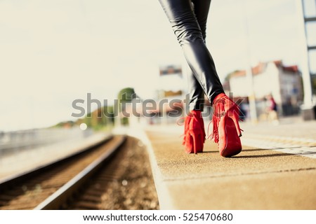 Woman in red high heels walking in train station #525470680