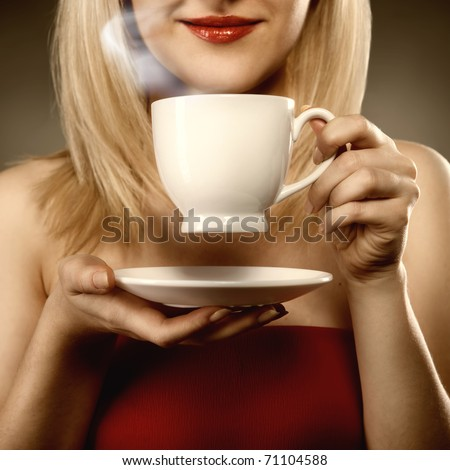 woman in red holding cup and smiles