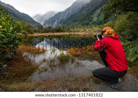 Woman in red jacket taking picture of Reflection lake on west coast New Zealand