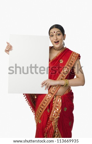 Woman in red mekhla holding a placard