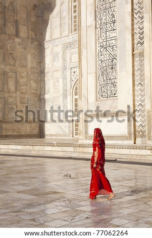 Woman in red saree/sari walking past the Taj Mahal.