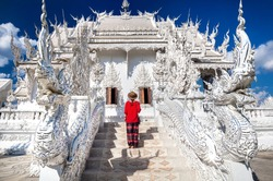 Woman in red shirt in front of Wat Rong Khun The White Temple in Chiang Rai, Thailand