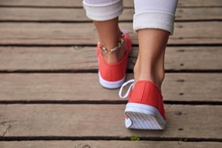 Woman in red shoes and white jeans on wooden boards.