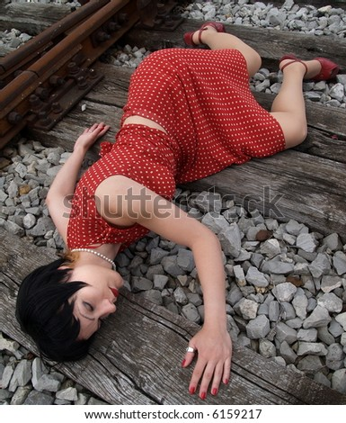 Woman in red skirt lying on the railroad