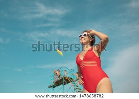 woman in red swimsuit in white sunglasses blue sky on background copy space looking forward