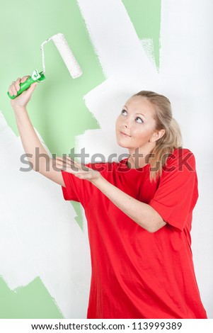 Woman in red t-shirt showing on paint roller in hand
