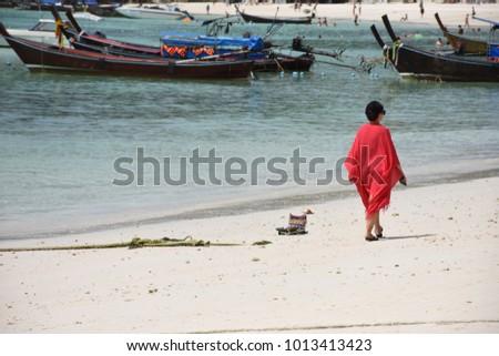 Woman in red vestment walk alone on beach.  - Shutterstock ID 1013413423