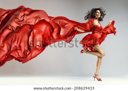Woman in red waving dress with flying fabric #208629433