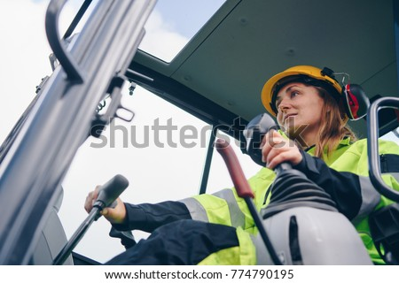 Woman in reflective clothing operating heavy equipment #774790195