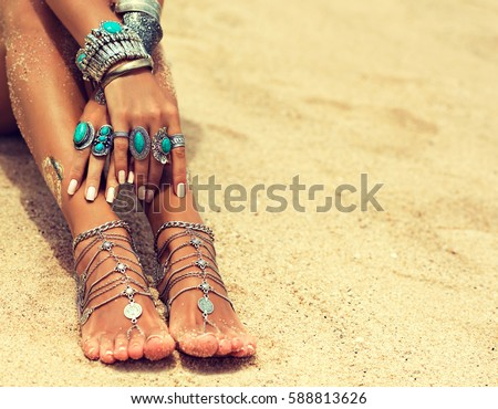 Woman In Relaxation On Tropical Beach with sand , body parts  . Tanned girl in Lotus position with silver jewelry,bracelets and rings with turquoise.Boho style
