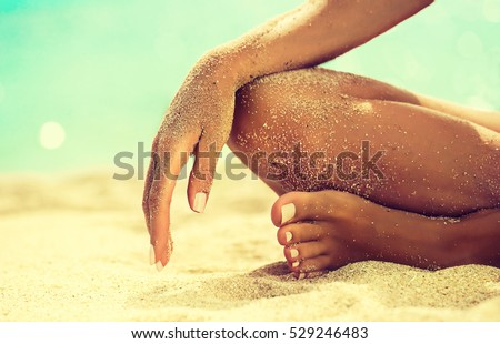 Woman In Relaxation On Tropical Beach with sand , body parts  . Tanned girl in Lotus position,yoga, and meditation