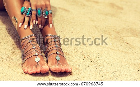 Woman In Relaxation On Tropical Beach with sand , body parts  . Tanned girl leg with silver jewelry,bracelets and rings with turquoise.Boho style feet and hands #670968745