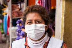 Woman in repiratory mask during coronavirus pandemic in market in Cusco, Peru in Latin South America. Epidemic of coronavirus covid-19