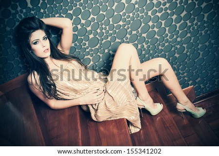 woman in retro style golden dress and high heel shoes sit on stairs full body shot indoor