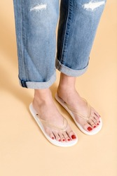 Woman in ripped jeans standing on a beige background