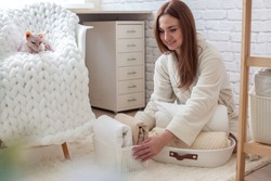Woman in robe is sitting near wooden shelving, organizing closet by sorting and folding bath towels and placing into white wicker basket while touching white colored Don Sphynx cat. Spring cleaning.