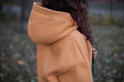 Woman in sand color oversized hoodie standing back view.a girl stands in oversize hoodie.fashion and wear concept. oversized wear at girl.warm oversize wear at female.space for text and logo. close up