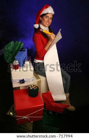 woman in santa hat is double checking her list for the holidays surrounded by gifts in a misty blue background