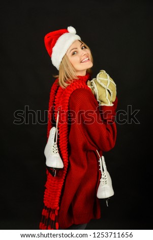 a6068bf8ab0 Woman in Santa hat with ice skate. Happy girl in warm sweater with figure  skates
