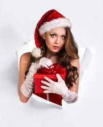 Woman in santa's costume tears up from paper hole