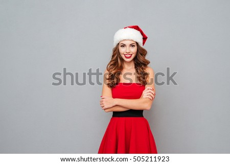 Woman in santa's hat and dress with arms crossed over gray background stock photo