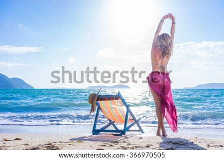 Woman in sarong stretching on the tropical beach in Thailand #366970505