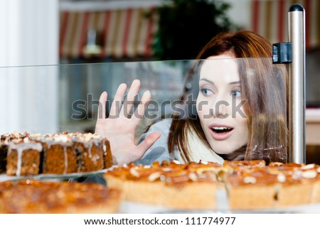 Woman in scarf looking at the bakery window full of different pieces of tarts