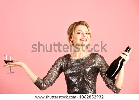 Woman in shining dress with alcohol on pink background. Girl with smiling face drinks expensive cabernet or merlot. Winetasting concept. Lady holding glass and bottle of red Italian wine. #1062852932