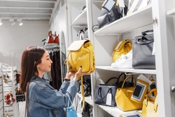 woman in shop choosing leather bags and backpacks, fashion accessories and shopping concept