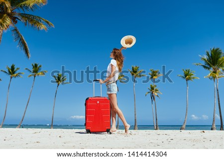 Woman in shorts and t-shirt with a red suitcase of hat in hand on an island with palm trees            #1414414304