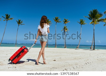 woman in shorts with a suitcase walks along the ocean shore, travel tourism tropics          #1397138567