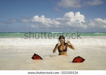 Woman in snorkeling gear sitting in surf