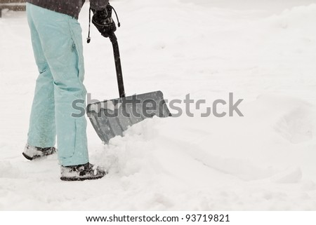 woman in snow suit shoveling and cleaning the driveway after a snow storm