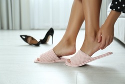 Woman in soft slippers at home, closeup. Tired feet after wearing high heels