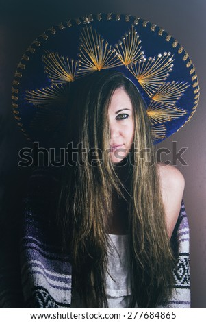 Woman in Sombrero. A beautiful woman wearing a sombrero and wrapped in a Mexican blanket.