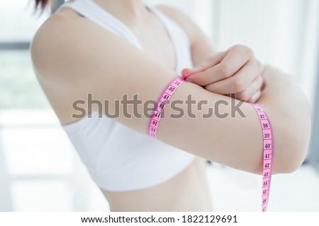 Woman in sport bra measuring upper arm ストックフォト ©