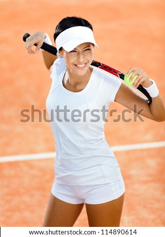 Woman in sports wear keeps tennis racket and ball on her shoulders at the clay tennis court. Competition