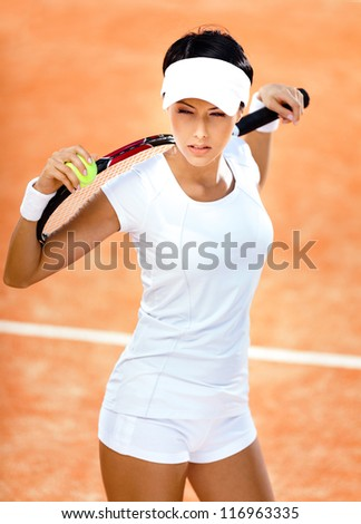 Woman in sports wear keeps tennis racket and ball on her shoulders at the clay tennis court. Tournament