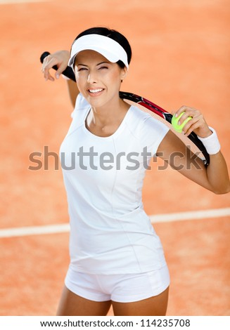 Woman in sports wear keeps tennis racket and ball on her shoulders at the clay tennis court. Contest