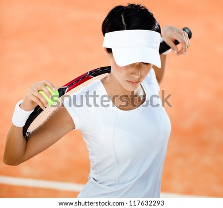 Woman in sports wear keeps tennis racket and ball on her shoulders at the clay tennis court. Leisure