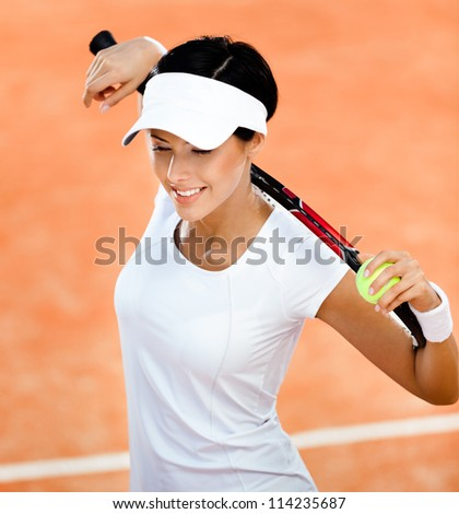Woman in sports wear keeps tennis racket and ball on her shoulders at the clay tennis court. Match
