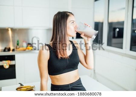 Woman in sportswear drinking sweet banana chocolate protein powder milkshake smoothie.Drinking protein after at home workout.Whey, banana and low fat milk sports nutrition diet.Healthy lifestyle