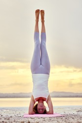 Woman in sportswear perform asana on nature near salt lake during picturesque sunset, yogi female doing Hatha yoga headstand or Sirsasana front full-length vertical view, balance of body mind concept