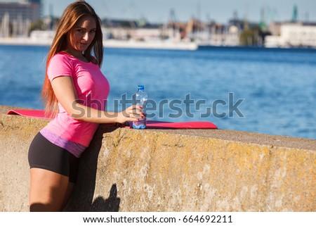 Woman in sportswear takes a break to rehydrate drinking water from plastic bottle, resting after sport workout outdoor by seaside #664692211