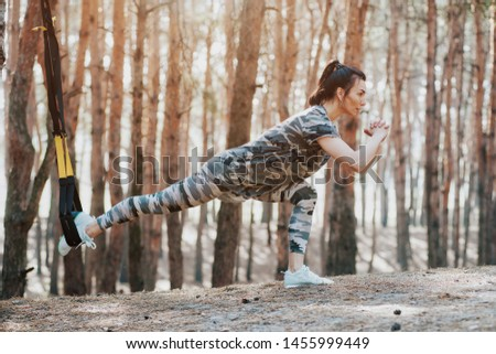 woman in sportswear the color of military trains in the woods on the trx straps