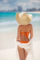 Woman in straw hat and orange bikini on a tropical beach. view of female back on a background of the ocean. Young woman in white walking on ocean beach