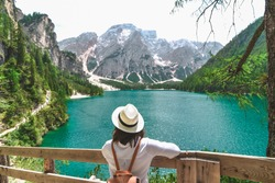 woman in straw hat with backpack standing and looking at lake in dolomites alps