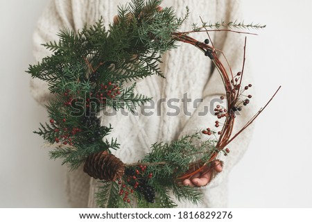 Woman in stylish knitted sweater holding modern christmas wreath on white background. Rustic christmas wreath in female hands with fir branches, berries and cone. Merry Christmas Сток-фото ©
