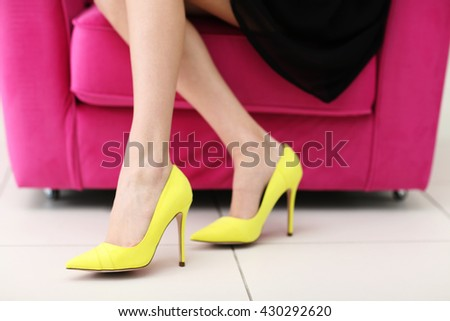 Woman in stylish shoes on pink armchair